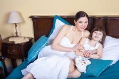 Relación ideal en familia La mamá y la hija mienten en cama en Foto de archivo