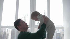 relacionamento da Pai-criança, paizinho novo que joga com o menino da criança que aumenta nos braços contra a janela na luz natur video estoque