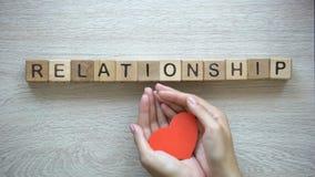 Relacionamento, mulher que guarda o coração de papel sob a palavra de cubos de madeira, amor puro video estoque