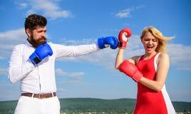 Relaciones como concepto de la lucha El hombre y la mujer luchan el fondo del cielo azul de los guantes de boxeo Defienda su opin imagen de archivo libre de regalías
