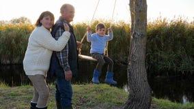 Relaciones mutuas del niño y de los adultos, ocio de la gente feliz cerca del río entre las cañas en luz del sol brillante metrajes