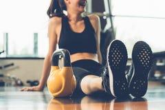 Relajándose, mujer feliz que se sienta con pesas de gimnasia después de entrenamiento foto de archivo libre de regalías