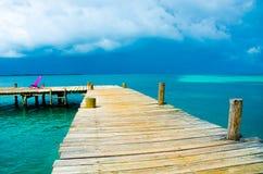 Relaj?ndose en la silla - Belice Cayes - peque?a isla tropical en la barrera de arrecifes con la playa del para?so - sabida para  imágenes de archivo libres de regalías