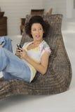 Relajación adentro con el teléfono celular Imagen de archivo libre de regalías