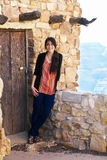 Relajación adolescente Biracial de la muchacha, inclinándose contra overlooki de la pared de la roca Foto de archivo