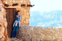 Relajación adolescente Biracial de la muchacha, inclinándose contra overlooki de la pared de la roca Imágenes de archivo libres de regalías