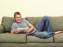 Relajación adolescente con la tablilla Fotos de archivo