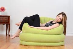 Relajación adolescente en silla verde del puf Imagen de archivo