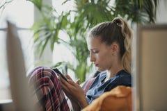 Relajación adulta joven en su teléfono Foto de archivo libre de regalías