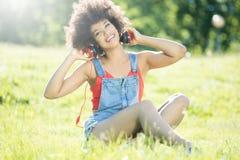 Relajación afroamericana de la muchacha al aire libre con los auriculares Imágenes de archivo libres de regalías