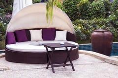 Relajación cerca de la piscina hermosa: sofá de lujo con el pi fotografía de archivo