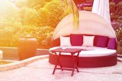Relajación cerca de la piscina hermosa: sofá de lujo con el pi foto de archivo
