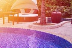 Relajación cerca de la piscina hermosa: sofá de lujo con el pi imagenes de archivo