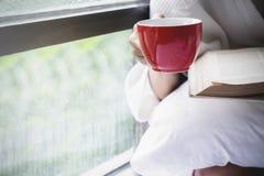 Relajación con café caliente y lectura de un libro en la cama en el MES Fotos de archivo