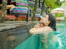 Relajación coreana asiática atractiva y hermosa joven de la mujer feliz en la natación tropical del complejo playero en la piscin imagen de archivo libre de regalías