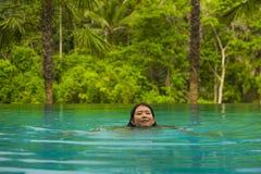 Relajación coreana asiática atractiva y hermosa joven de la mujer feliz en la natación tropical del complejo playero en la piscin imagen de archivo