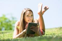 Relajación de la muchacha al aire libre con la tableta Fotos de archivo libres de regalías