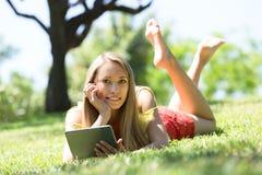 Relajación de la muchacha al aire libre con la tableta Fotografía de archivo