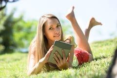 Relajación de la muchacha al aire libre con la tableta Fotografía de archivo libre de regalías