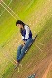 Relajación de la muchacha en el oscilación Imagenes de archivo
