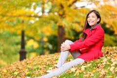 Relajación de la mujer de la caída feliz en follaje del bosque del otoño Imagenes de archivo
