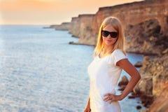 Relajación de la mujer joven al aire libre con puesta del sol azul del mar y de las rocas en fondo Imagen de archivo