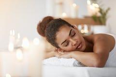 Relajación de reclinación de la muchacha africana blanda con los ojos cerrados en salón del balneario Fotos de archivo