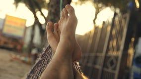 Relajación debajo de las palmas en la playa en la puesta del sol Pies que balancean en una hamaca, POV almacen de video