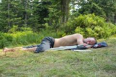 Relajación del hombre del caminante, mintiendo en un claro en bosque conífero y el sl Imagen de archivo