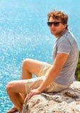 Relajación del hombre joven al aire libre en el acantilado rocoso que se sienta y que mira encendido fotografía de archivo