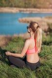 Relajación después de entrenar Chica joven atractiva en el sportwear de moda que se sienta en hierba y que hace la meditación en  Imagenes de archivo