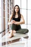 Relajación después de entrenar Opinión la mujer joven hermosa que mira ausente mientras que se sienta en la estera del ejercicio  Foto de archivo libre de regalías