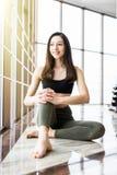 Relajación después de entrenar Opinión la mujer joven hermosa que mira ausente mientras que se sienta en la estera del ejercicio  Imagen de archivo libre de regalías