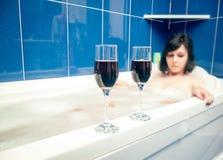 Relajación en el cuarto de baño con el vino imagenes de archivo