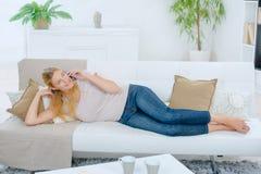 Relajación en el sofá con el móvil Foto de archivo libre de regalías