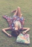 Relajación en hierba La opinión superior la mujer joven hermosa en gafas de sol y el pareo que miente en la hierba verde con la p Foto de archivo