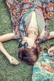 Relajación en hierba La opinión superior la mujer joven hermosa en gafas de sol y el pareo que miente en la hierba verde con la p Fotografía de archivo libre de regalías