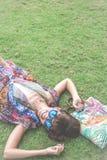 Relajación en hierba La opinión superior la mujer joven hermosa en gafas de sol y el pareo que miente en la hierba verde con la p Imagen de archivo