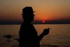 Relajación en la puesta del sol por el mar Fotos de archivo