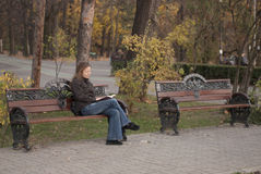 Relajación en un parque que lee un libro Imágenes de archivo libres de regalías