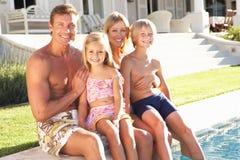 Relajación exterior de la familia por la piscina imagen de archivo