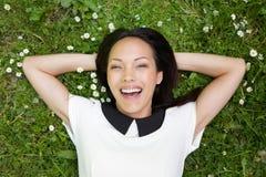 Relajación femenina asiática en hierba y sonrisa Foto de archivo libre de regalías