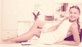 Relajación femenina joven alegre en el escritorio con los documentos Imagen de archivo libre de regalías