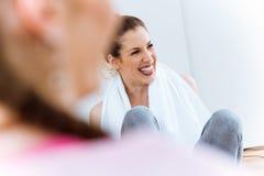 Relajación femenina joven en la estera de la yoga y el hablar después de sess del entrenamiento Foto de archivo