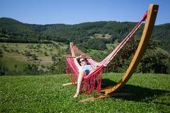 Relajación femenina joven en una hamaca Imagen de archivo
