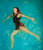 Relajación flotante de la mujer en agua de la piscina Imagenes de archivo