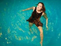 Relajación flotante de la mujer en agua de la piscina Imagen de archivo libre de regalías