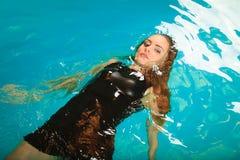 Relajación flotante de la mujer en agua de la piscina Foto de archivo libre de regalías
