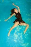Relajación flotante de la mujer en agua de la piscina Foto de archivo