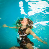Relajación flotante de la mujer en agua de la piscina Imagen de archivo